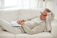 Homme supérieur dormant sur le sofa avec le livre à la maison Photographie stock libre de droits