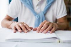 Homme supérieur employant Braille pour lire Images libres de droits