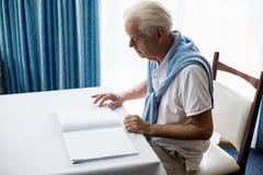 Homme supérieur employant Braille pour lire Image stock