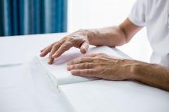 Homme supérieur employant Braille pour lire Photographie stock
