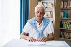 Homme supérieur employant Braille pour lire Photographie stock libre de droits