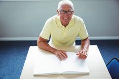 Homme supérieur employant Braille pour lire Photo stock