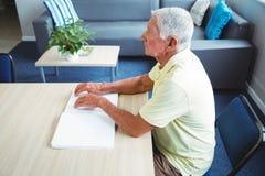 Homme supérieur employant Braille pour lire Photos stock