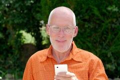 Homme supérieur en bonne santé sur le jardin extérieur de téléphone Photographie stock libre de droits