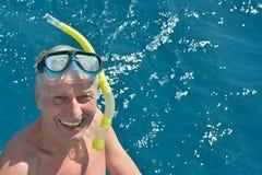 Homme supérieur en mer avec le masque naviguant au schnorchel Images libres de droits