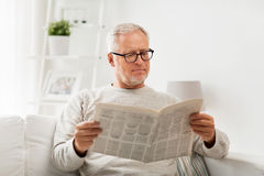 Homme supérieur en verres lisant le journal à la maison Images libres de droits