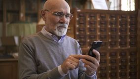 Homme supérieur en verres ronds utilisant son smartphone banque de vidéos
