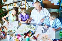 Homme supérieur enseignant Art Class à l'école photos stock
