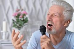 Homme supérieur enthousiaste tenant le microphone Photographie stock
