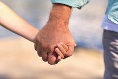 Homme supérieur et enfant tenant des mains Photos libres de droits