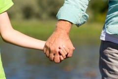 Homme supérieur et enfant tenant des mains Photo stock