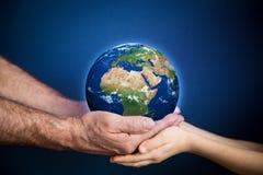 Homme supérieur et enfant tenant la planète de la terre dans des mains Image stock
