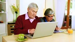 Homme supérieur et femme avec l'ordinateur banque de vidéos
