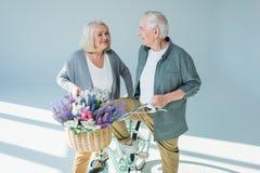 Homme supérieur et femme heureux avec la bicyclette Photo stock