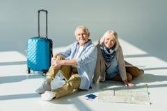 Homme supérieur et femme s'asseyant sur le plancher avec la carte, les passeports et les billets de déplacement Photo libre de droits