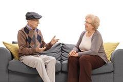Homme supérieur et femme s'asseyant sur un sofa et parler Image stock