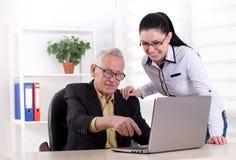 Homme supérieur et jeune femme regardant l'ordinateur portable Images stock