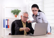 Homme supérieur et jeune femme regardant l'ordinateur portable Image libre de droits