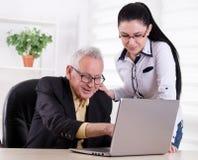 Homme supérieur et jeune femme regardant l'ordinateur portable Photos libres de droits
