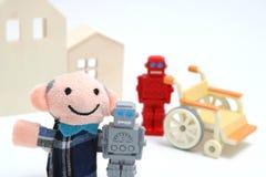 Homme supérieur et robots avec le fauteuil roulant sur le fond blanc Soin infirmier et concept d'assistant de robot Photos stock