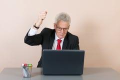 Homme supérieur fâché contre le bureau Image stock