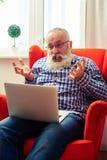 Homme supérieur fâché regardant l'ordinateur portable Photo libre de droits