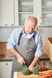 Homme supérieur faisant cuire comme passe-temps images stock