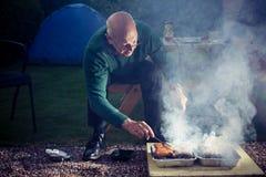 Homme supérieur faisant cuire sur un barbecue Image stock