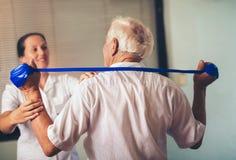 Homme supérieur faisant des exercices utilisant une courroie Photographie stock