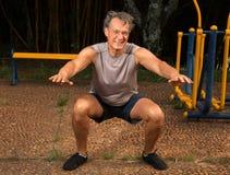 Homme supérieur faisant des postures accroupies Photographie stock