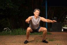 Homme supérieur faisant des postures accroupies dehors Photographie stock