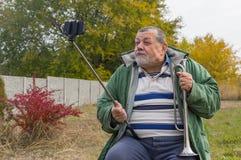 Homme supérieur faisant des visages tout en faisant le selfie extérieur Image stock