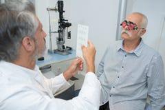 Homme supérieur faisant examiner des yeux par l'ophtalmologiste photos stock