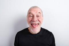 Homme supérieur faisant le visage drôle, collant la langue, tir de studio Photos libres de droits