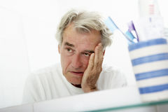 Homme supérieur fatigué regardant la réflexion dans le miroir de salle de bains Images libres de droits