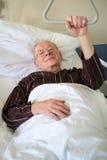 Homme supérieur fragile se situant dans un lit d'hôpital Photographie stock libre de droits