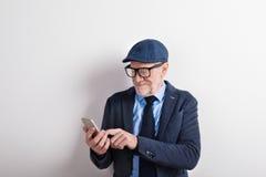 Homme supérieur futé dans le costume, les lunettes et le chapeau, tenant le smartphone Photos libres de droits