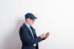 Homme supérieur futé dans le costume, les lunettes et le chapeau, tenant le smartphone Image libre de droits