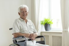 Homme supérieur handicapé de sourire dans seul un fauteuil roulant à la maison photos libres de droits
