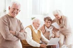 Homme supérieur heureux avec des amis Image stock