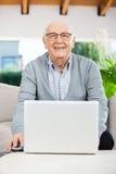 Homme supérieur heureux avec l'ordinateur portable au porche de maison de repos Photo stock