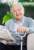 Homme supérieur heureux avec le journal et le Cane Sitting Photo libre de droits