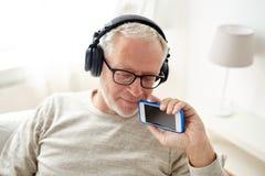 Homme supérieur heureux avec le smartphone et les écouteurs photo stock
