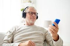 Homme supérieur heureux avec le smartphone et les écouteurs images stock