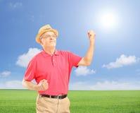 Homme supérieur heureux avec les mains augmentées faisant des gestes le bonheur Photographie stock libre de droits