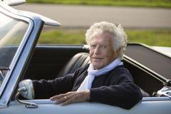 Homme supérieur heureux dans la voiture de sport de vintage Photographie stock libre de droits
