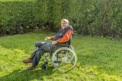 Homme supérieur heureux de sourire s'asseyant dans son jardin photos libres de droits
