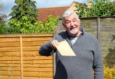 Homme supérieur heureux donnant une enveloppe brune simple Photographie stock