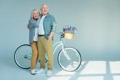Homme supérieur heureux et femme tenant la bicyclette proche Images stock