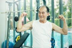 Homme supérieur heureux montrant son biceps au gymnase Photo stock